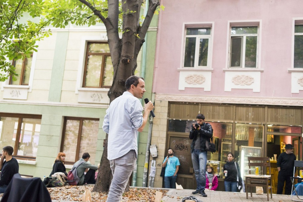 <p>Gavin Kroeber presenting <em>Dustbins of History.</em> Experience Economies, <em>At Home He's a Tourist</em>, 2014. One Architecture Week, Plovdiv. Photo courtesy of One Architecture Week.</p>